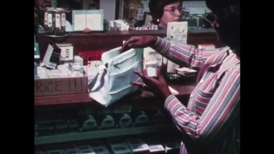 1970s: UNITED STATES: lady in shop. Lady puts medicine in handbag. Toddler takes medicine from handbag. Baby climbs up table. Lady moves bottle away from baby
