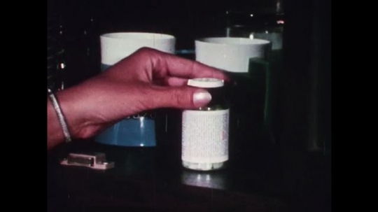 1970s: UNITED STATES: medicine in bottle. Tablets on shelf. Lady takes tablet with water. Girl sits and leans n arm