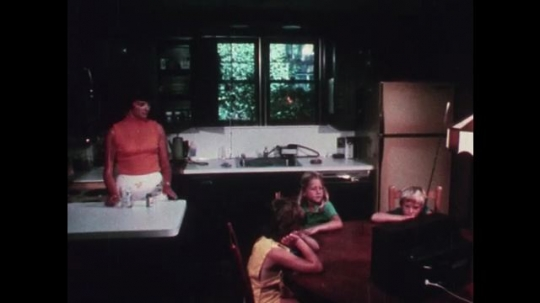 1970s: UNITED STATES: children listen to radio. Lady leaves room. Girl takes lady's tablets. Children gather around pills