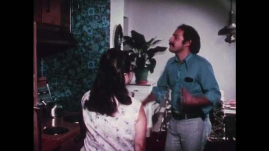 1970s: UNITED STATES: parents argue in kitchen. People carry boxes into house. Family moves house. Man unpacks box. Girl finds containers in box