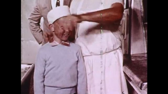 1960s: Baker puts white hat on boy, boy pushes button on machine. Machine sifts flour. Bread ingredients labeled on counter. Baker stands by industrial mixer.