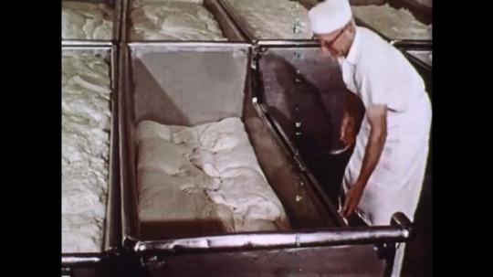 1960s: Baker latches side of dough bin. Bins of dough. Large machine cuts dough, man pulls dough out of bowl.