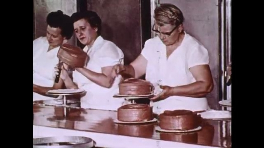 1960s: Women ice cake in bakery. Woman spreads chocolate icing on cake. Wheel of colored icing spins, worker scoops icing onto cake. Workers decorate cakes.