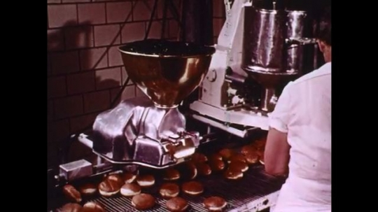1960s: Bakery worker holds doughnuts up to needles on machine, injects doughnuts with jelly. Machine drops dough rings into hot oil. Boy watches doughnuts float by in oil. Boy smiles.