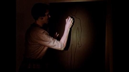 1950s: Woman draws outline of body on chalkboard in felt pen. Woman paints board with black chalkboard paint.