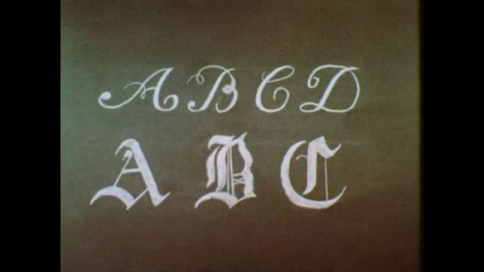 1950s: Italic and Old English script of ABCD on chalkboard. Plain upper and lower case letters ABCDEF in chalk. Woman writes