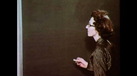 1950s: Woman writes cursive letter on chalkboard. Teacher in front of class writes