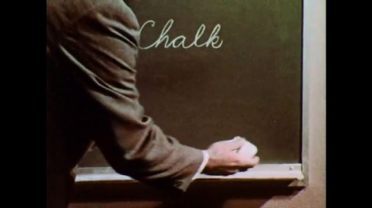 1950s: Man wipes chalkboard with rag in circular motion, shows dirty rag, lathers foam in circles. Man wipes chalkboard clean in straight swipes.