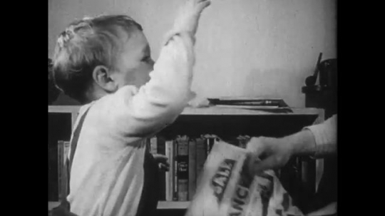 1950s: Toddler hits newspaper and Father talks angrily. Father lights pipe and sits with Mother on couch talking. Mother puts toddler on toilet. Toddler cries and wipes face.