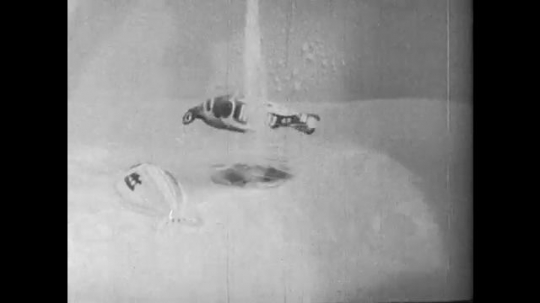 1950s: UNITED STATES: lady looks into cot. Toy in bath as water runs from tap. Loud noise and marching band in street. View from pushchair