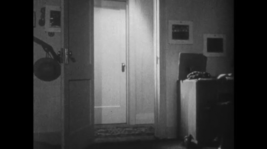 1950s: UNITED STATES: view across bedroom. Light on in hall. Bedroom door open. Darkness inside cupboard.