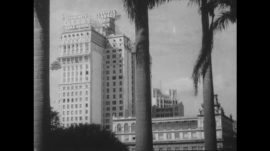 S?o Paulo, Brazil, 1930s: Buildings and palm trees. People walk on sidewalk past building. People pass opera house in street, two on horse.