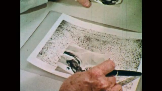 1970s: Hands hold images of brain.  Hand gestures with pen.