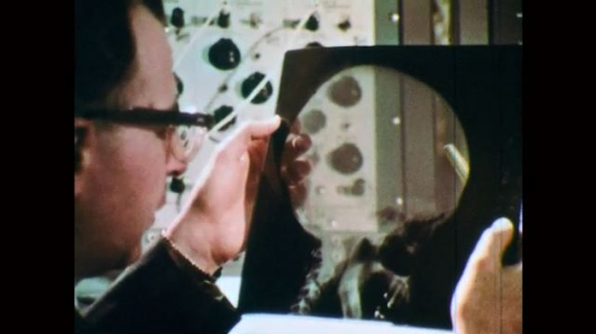 1970s: Man holds up x-ray of skull.  Man holds image.  Man points.  Men talk.