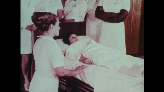 1970s: Man and nurses stand around hospital bed.  Woman kneels.  Nurse moves patient to edge of bed and lowers onto floor.  Nurse wraps woman in blanket.  Woman drags patient.