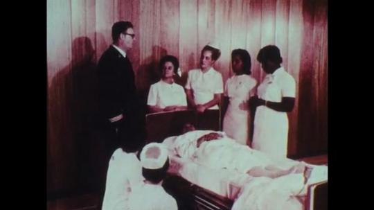 1970s: Man talks to nurses around hospital bed.  Women kneel.  Patient lies in bed.  Nurse puts arm under patient