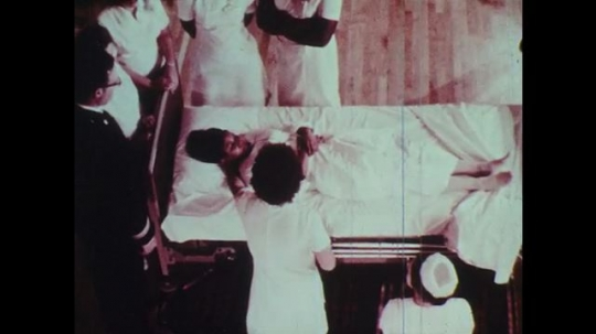 1970s: Man talks to nurses around hospital bed.  Nurse puts arms under patient