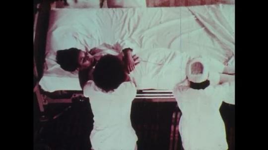 1970s: Nurses lower patient to the floor from hospital bed.  Women wrap patient in blanket.