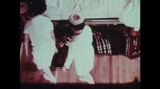 1970s: Nurses drag patient wrapped in blanket across floor.
