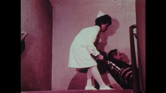 1970s: Nurse drags patient wrapped in blanket to the top of the stairs.  Tightly wrapped blanket.  Women look down stairs.