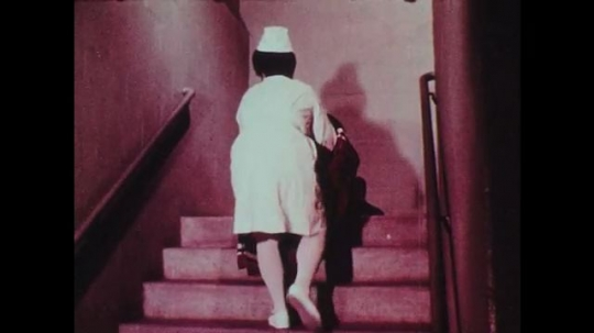 1970s: Nurse drags patient wrapped in blanket down staircase.