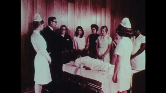 1970s: Group of people including nurses and doctors are surrounding a woman lying on a bed while a man talks.