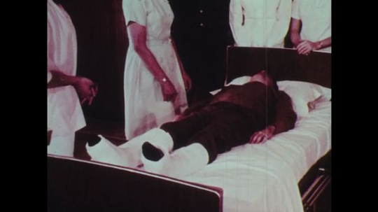 1970s: Two women nurses sit a man in leg casts upright in bed while holding him.