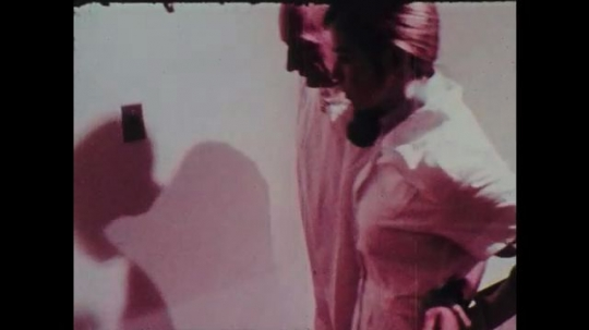 1970s: Female nurse helps patient walk down hallway. Female nurse puts another nurses arm around back of her waist.
