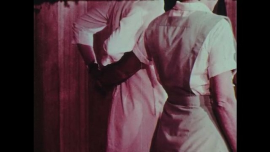 1970s: Two women nurses grab each other from behind waist and assist each other in walking.