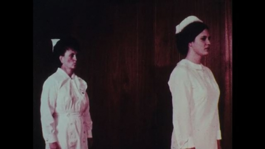 1970s: A female nurse stands behind another female nurse and grabs her arms from behind and crosses them.