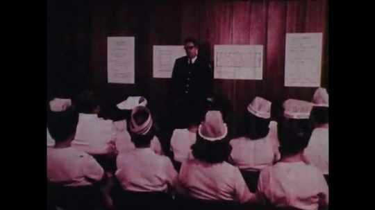 1970s: Man in medical uniform talks to seated medical staff.