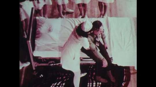1970s: Female nurse helps man out of bed and onto blanket on floor. She wraps blanket around man.