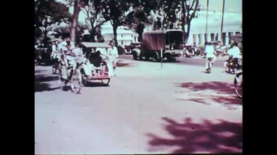 1950s: Bicycles and becaks drive down city street. Man in uniform directs city traffic.