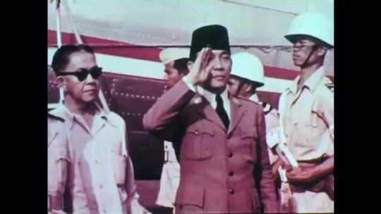 1950s: President Sukarno salutes. Indonesian flag waves. President Sukarno greets soldiers.