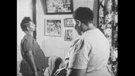 1950s: Women talk in living room. Woman looks at photographs on wall. Wall of baby photos. Woman points to frame and speaks. Woman responds and packs doctor bag.