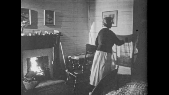 1950s: Woman opens door for midwife and man. People enter home. Man warms hands near fireplace.