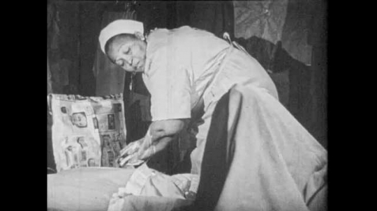 1950s: Shack, nurse washes hands, lathers soap up to elbows, turns to help pregnant woman lying in bed. Man sits waiting. Nurse calls man, man gets up.