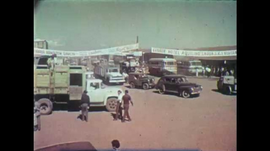 1950s: Vehicles move through small city.  People crowd around storefront.  Men examine fabric.