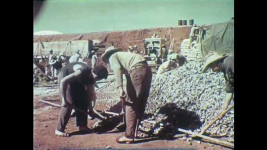 1950s: Construction site.  Men use shovels.  Men carry loads of rocks in teams.  Workers.  Cement mixers.