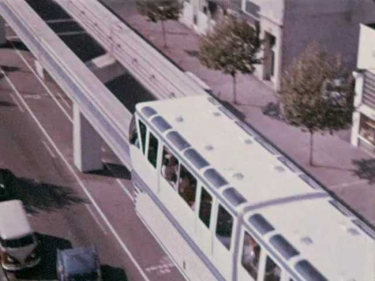 1960s: Man and woman ride through city on monorail, look out window point at amusements park ride, smile and laugh. Monorail pulls into station.