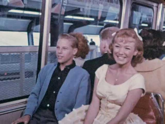 1960s: Man and woman exit passenger train along with other passengers.