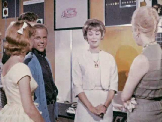 1960s: Woman talks to crowd of people at communications display. Man and woman smile and nod.