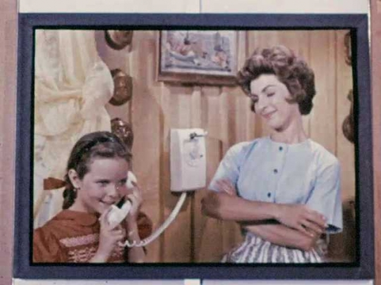 1960s: Girl on tv talks on phone. Spokeswoman talks. Woman on tv dials number into telephone.