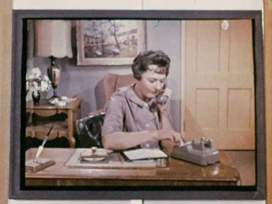 1960s: Woman on tv sits at desk, dials phone, talks.