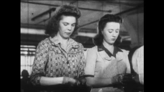 1940s: UNITED STATES: ladies build rifle cartridges at factory. Lady with pin on uniform.
