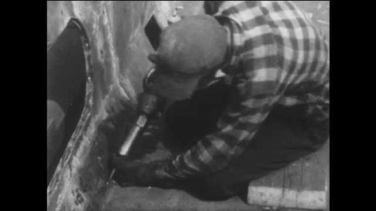 1940s: UNITED STATES: man welds metal at factory. Machinery turns over. Grease on machinery in factory