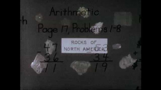 1960s: display of minerals with label of Rocks of North America. Drawing of Earth, Mars and Venus marked our planets. hands pull back cover of handwritten book report of Treasure Island on desk.