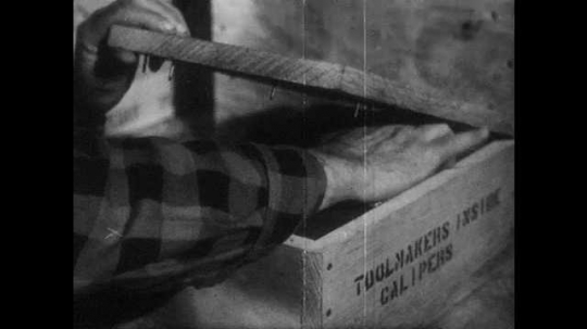 1950s: UNITED STATES: hand inside wooden box. Man shakes box. Man speaks on telephone. Man steals from box