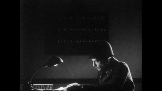 1950s: UNITED STATES: man works at desk. Lights on panel. Quiet alarm. Hand on packet tied with string