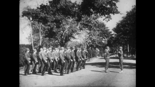 1950s: UNITED STATES: soldiers stand at attention on parade. Soldiers fall out.